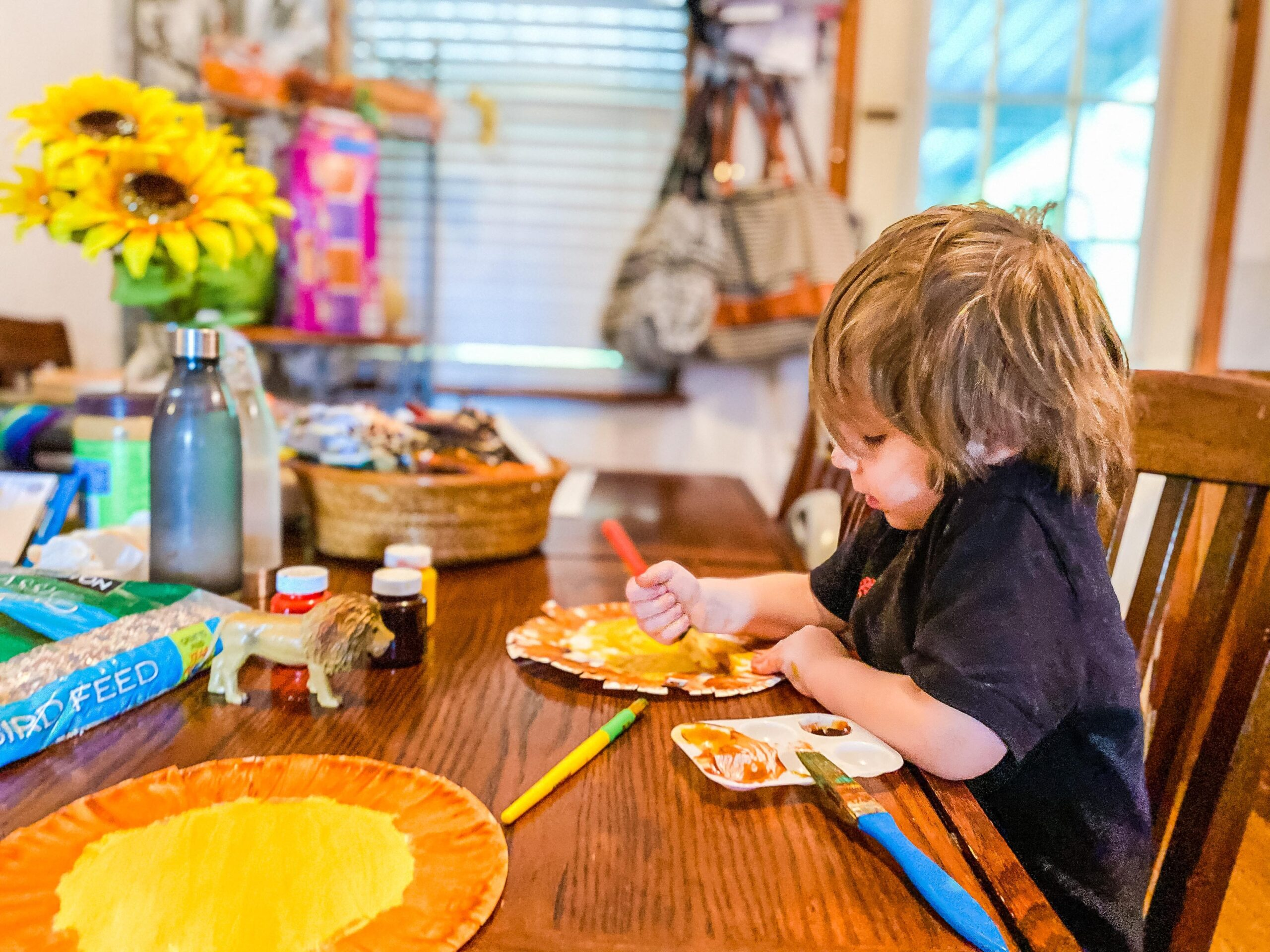 Preschooler painting a paper plate lion at a dining table