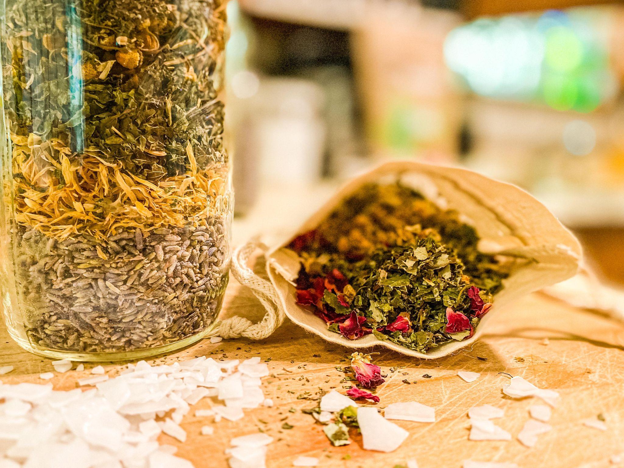 A muslin sack and mason jar full of herbal pregnancy bath blend