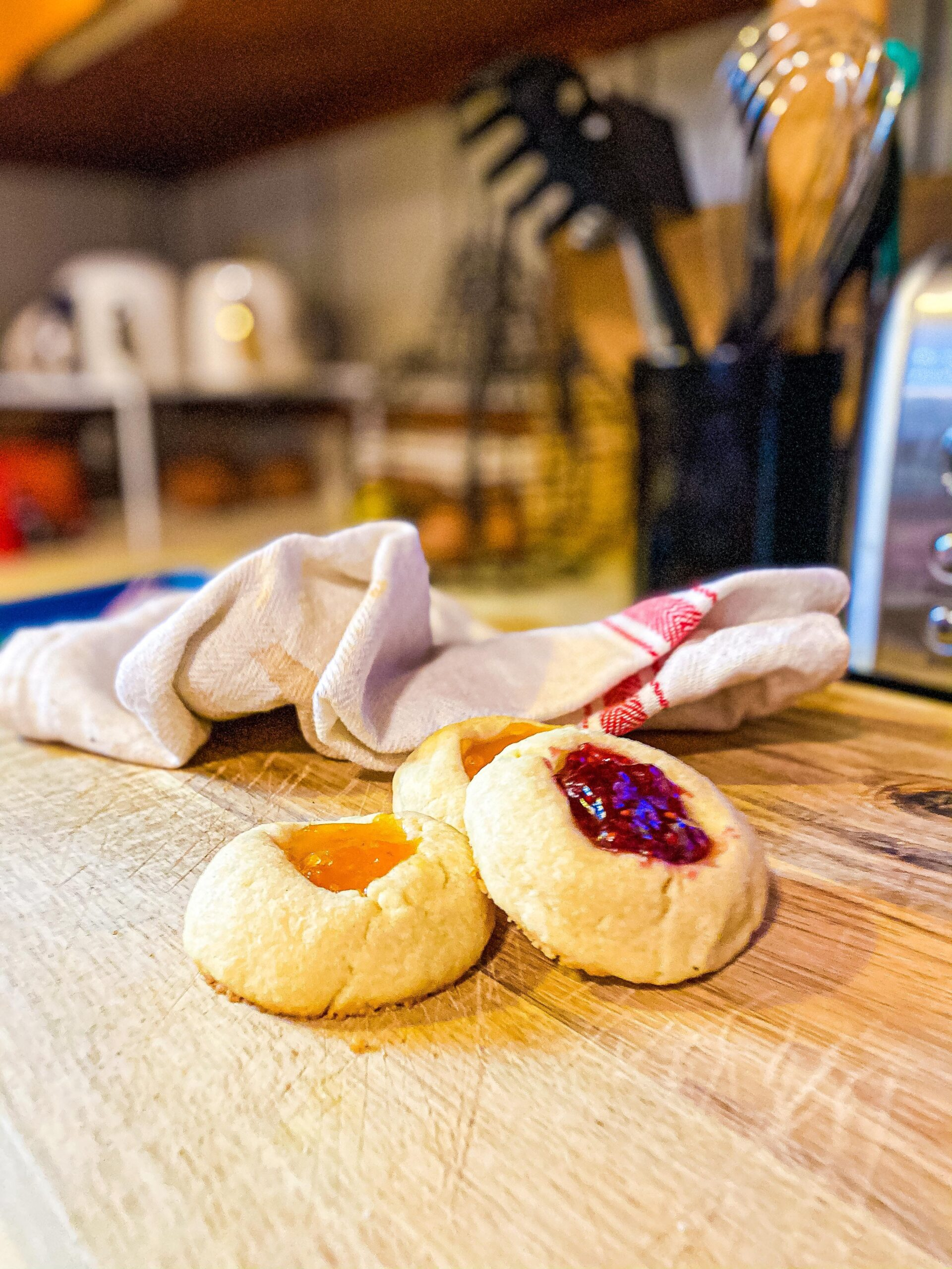 Thumbprint Cookies on a wooden cutting board in the kitchen with a hand towel