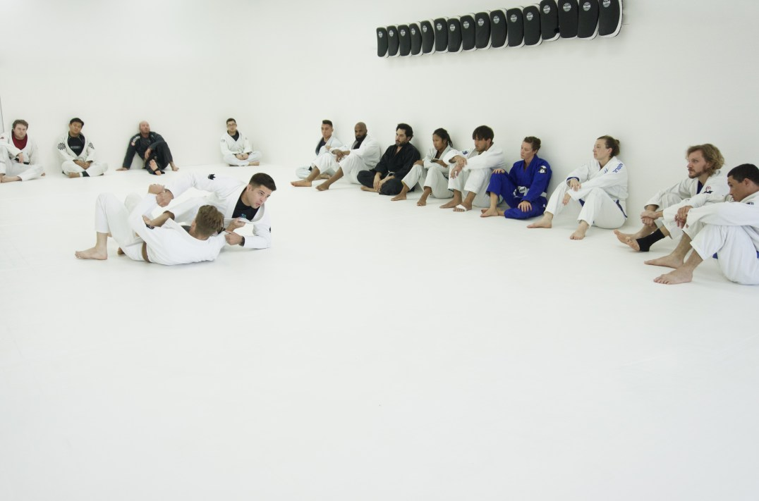 Head Instructor Justen Hamilton demonstrating Brazilian Jiu-Jitsu techniques in front of a full class