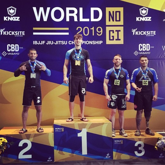 Coach Andrew on the podium after he wins IBJJF Masters 1 Blue Belt No-Gi Jiu-Jitsu Heavyweight Championship