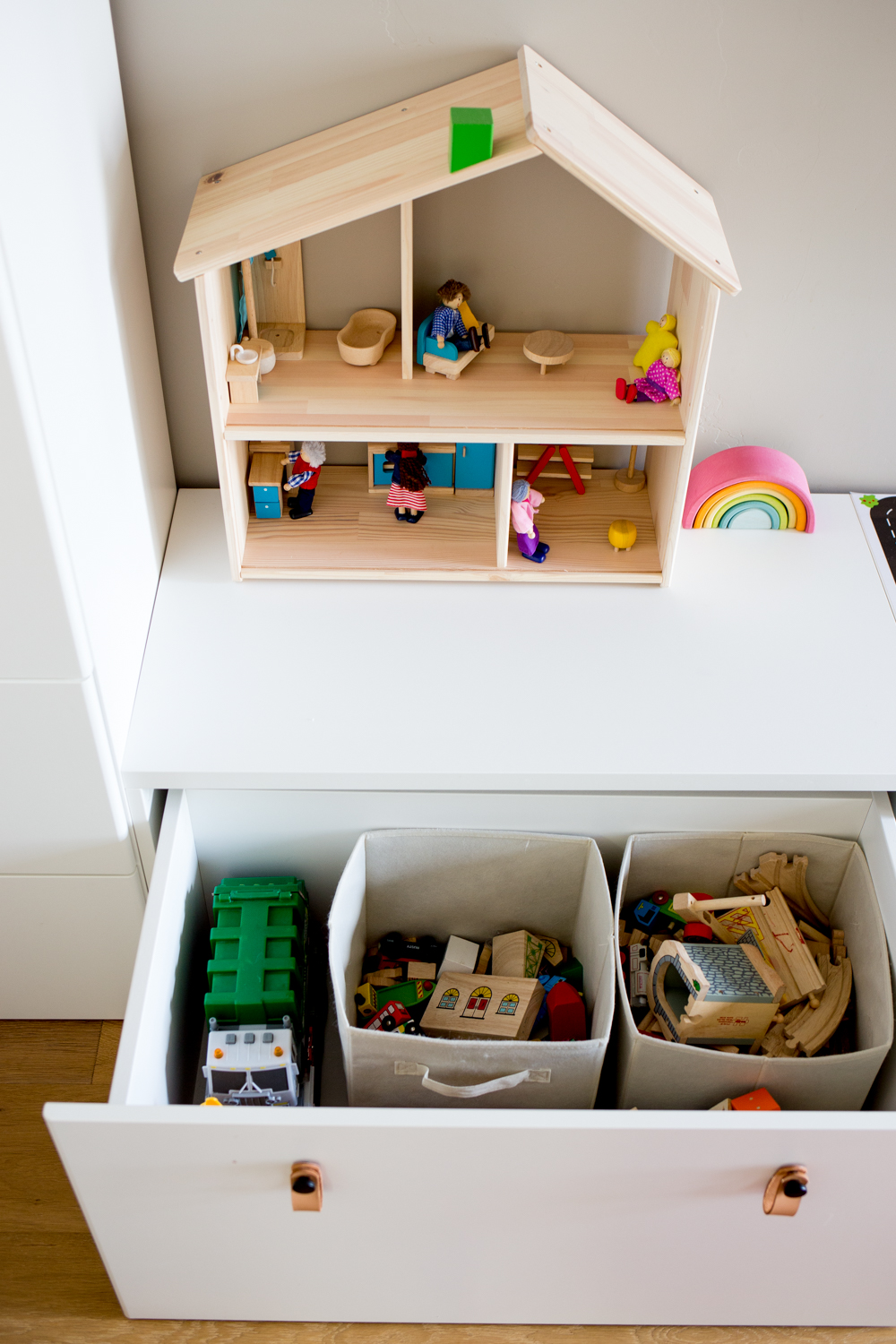 white modern toy storage bench IKEA with toys in open drawer and simple wooden dollhouse on top