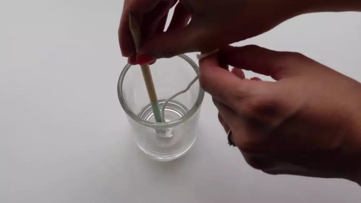 Nhúng phần cuối của bấc vào sáp nóng chảy rồi nhanh chóng gắn vào