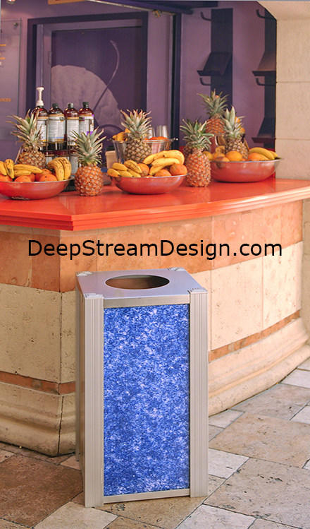 A modern trash receptacle by DeepStream Design with Blue Glass 3form panels in front of a colorful fruit drink stand
