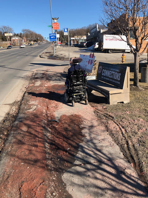 A hard to navigate sidewalk along Dodge Street is full of reddish sand and debris. A man in an electric wheelchair is trying to make his way up the street but is having a hard time. Wheel chair tracks are apparent in the soft mud next to the sidewalk because it's too difficult to make it by on the pavement.