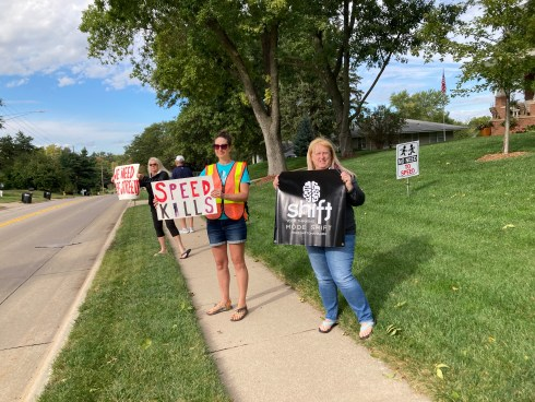 """A group of people are standing along a road holding signs that say """"We Need Safe Streets"""" and """"Speed Kills"""" as well as a black and white Mode Shift banner. In the background there's a yard with a black and white sign showing kids playing with the words """"No Need to Speed!"""" below."""