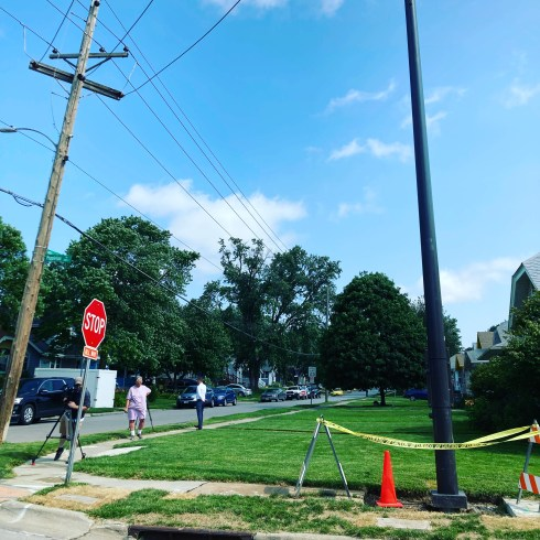 A torn up sidewalk with construction tape and cones around a sky-high Verizon cell tower right in the middle. The sky is blue with a few white clouds and the grass in the foreground is green. There's a news camera to the left, with a reporter talking to the home owner, Jane, wearing pink shorts and shirt.