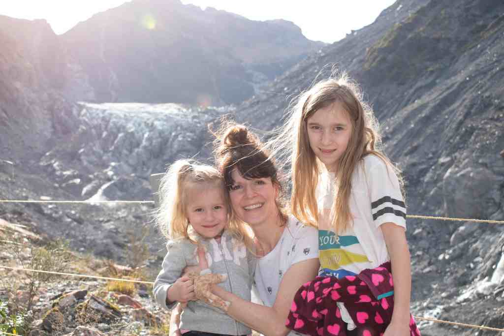 A woman and two young girls sit in the foreground with a distant view of Fox Glacier behind them. The receding Fox Glacier is visible from the glacier viewing area. Stone debris and slate are visible in much of the foreground, with only a small edge of the glacier still visible at the top of the valley.