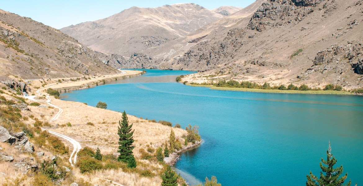 Turquoise blue-green water in the reservoir between Clyde Dam and the city of Cromwell, New Zealand, contrasts with dry, rocky hillsides beyond. The view looking back toward Clyde reveals a narrow dirt road below the main highway that snakes along the shoreline near scant trees and desert shrubs.