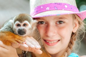 A young girl smiles as she holds a small monkey on her shoulder while wearing a pink-brimmed straw hat. The monkey is part of the various tourist attractions at the Pre-Colombian Mayan ruins of Tulum, Mexico, overlooking the Caribbean Sea on the Yucatan Peninsula.