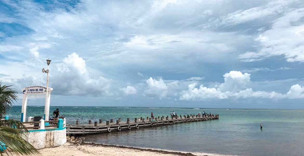 A small pier juts out into the Caribbean Sea in Mexico's Puerto Morelos, along the Riviera Maya. Clouds float over turquoise-blue water and white sand.