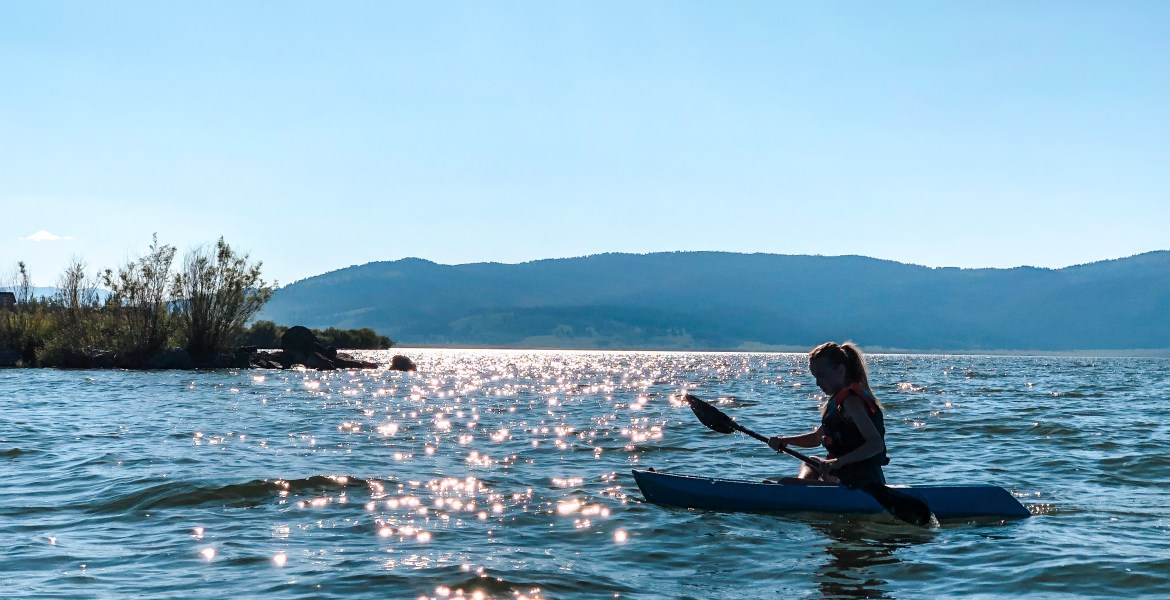 A young girl paddles her kayak across Henrys Lake in Northeastern Idaho, near Yellowstone National Park. She is silhouetted against the deep, blue water, and the sun shimmers and sparkles across the water. Blue sky and mountains can be seen in the distance, the edge of the Targhee National Forest.