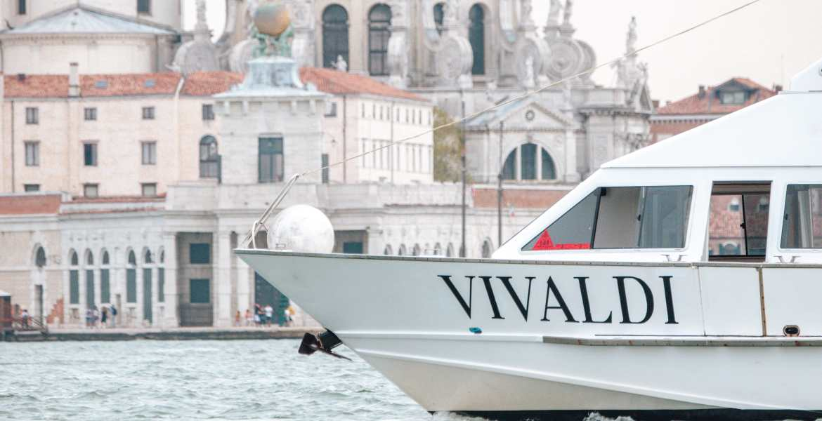 Venice Airport Transfer - Airport Water Taxi - A private water taxi approaches in the water near Venice, Italy. Wooden boats serve as private transportation throughout Venice, but are much more expensive than public transportation options