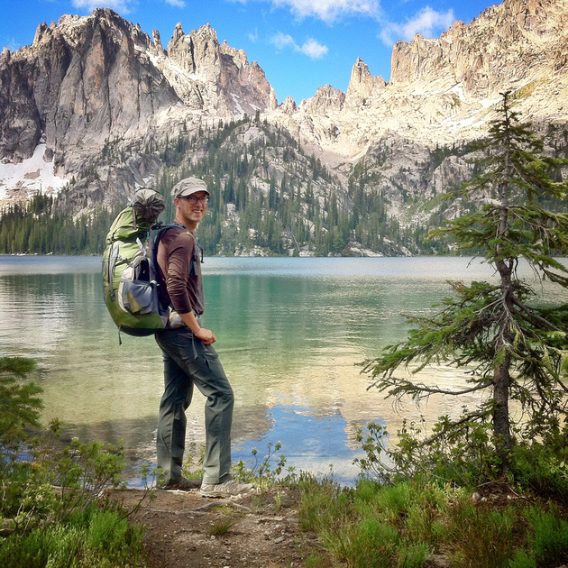 The Great PNW - Camping, Hiking, Hot Springs, and Other Things to do in the PNW. A backpacker stands at the edge of Baron Lake in Idaho's Sawtooth Wilderness Recreation Area.