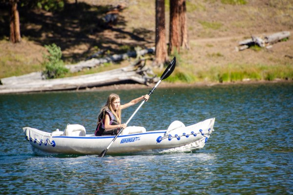 Best Place to Kayak - Magone Lake in Oregon. Several kayaks sit along the shore of Magone Lake, a natural lake created by a landslide in the early 1800s.