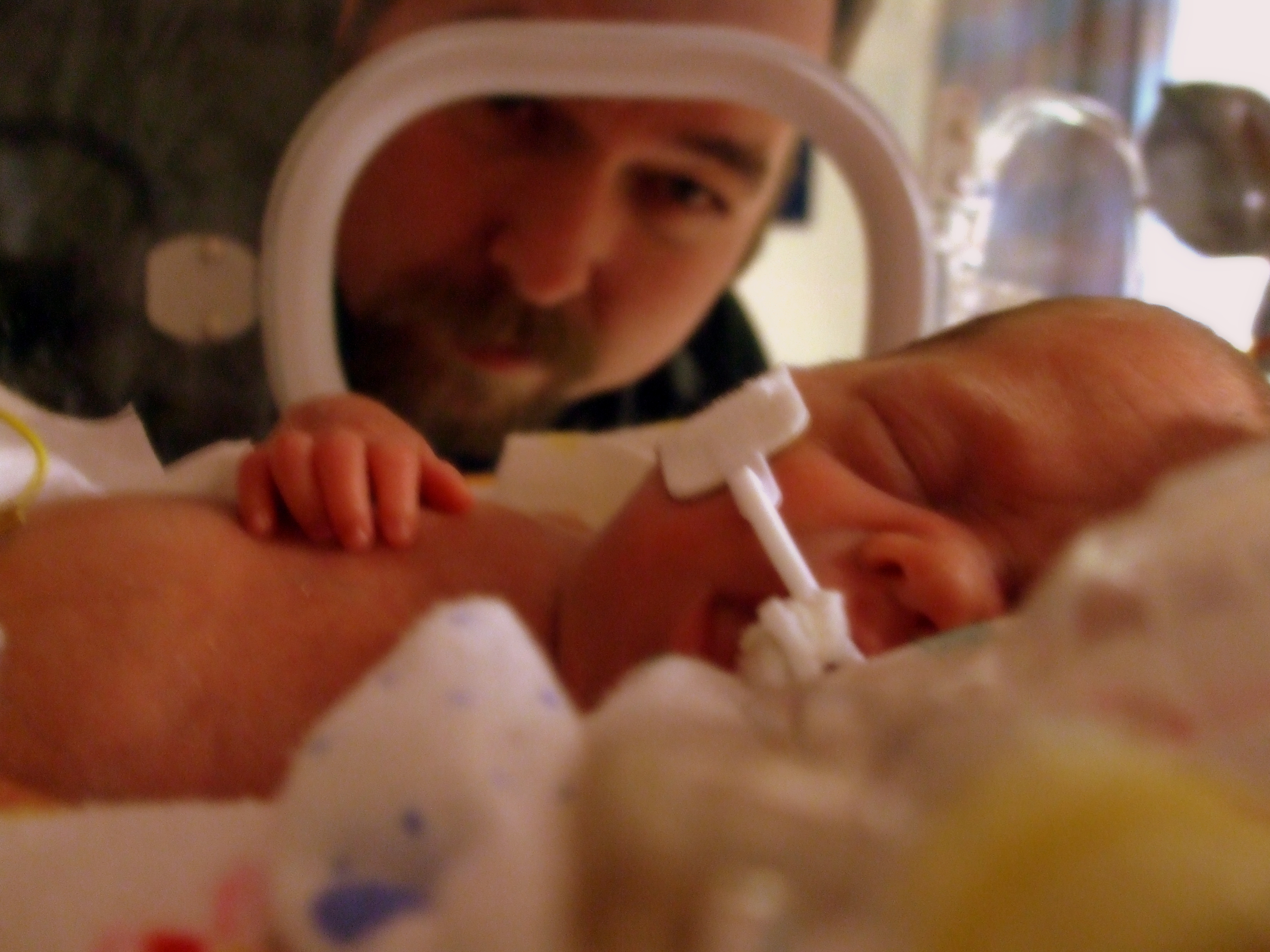 Photo: A father looks at his infant baby through an incubator in the NICU