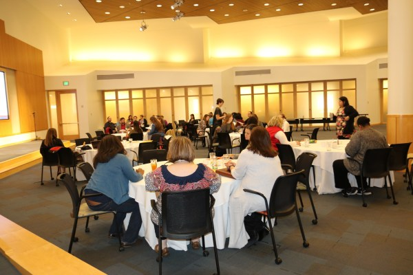 Photo: View of the back of the room, with all of the attendees visiting at tables at the November 2017 Family to Family Stakeholder's Meeting