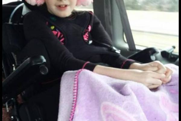Photo: Abby, wearing pink ear muffs with a pink blanket over her lap, rides in wheelchair-accessible van that was donated to her family.
