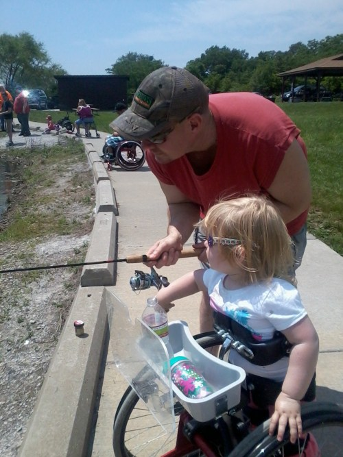 Photo: Dale helps Elizabeth fish at the park.