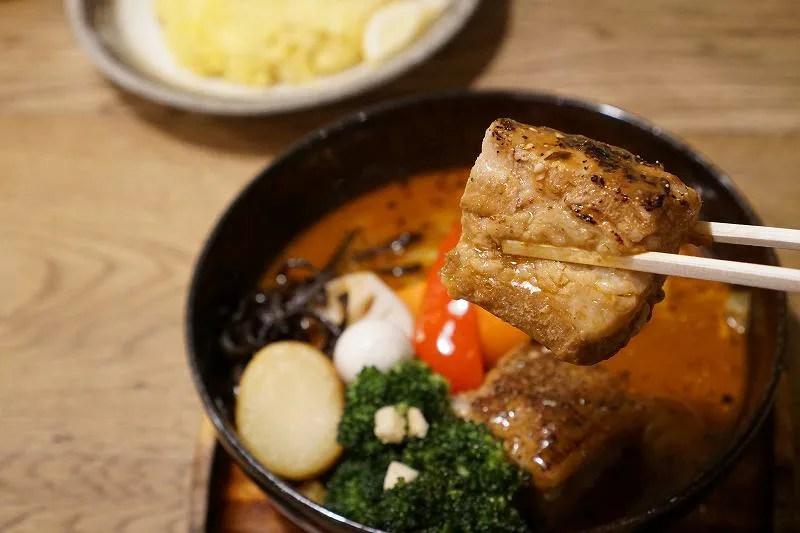 おおきな豚角煮を箸で持ち上げている様子