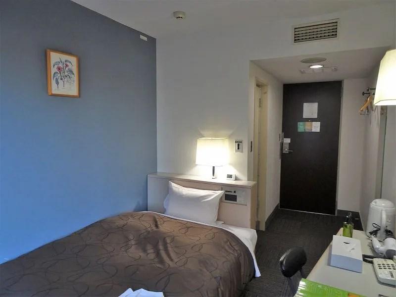 落ち着いたブルーの壁紙のホテルの客室のようす