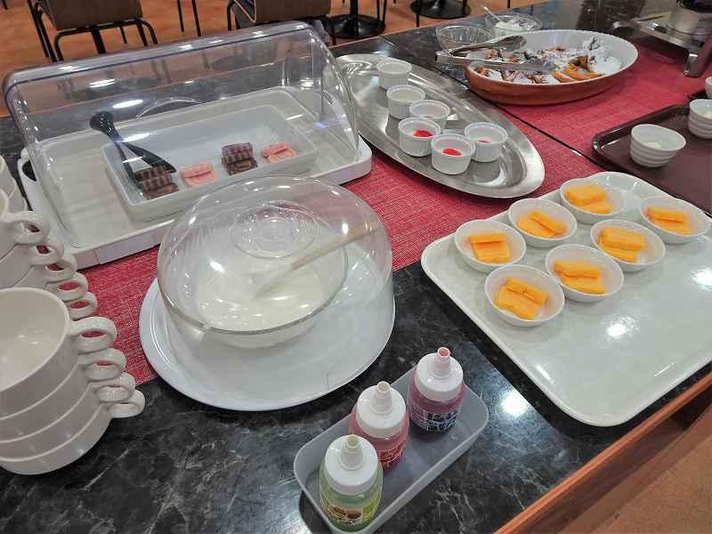 ヨーグルト、ロールケーキ、玉子焼きなどがテーブルに置かれている