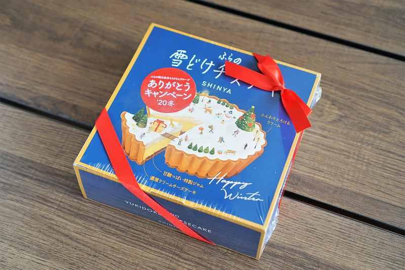 赤いリボンがかけられた「ふらの雪どけチーズケーキ」の青い箱がテーブルに置かれている