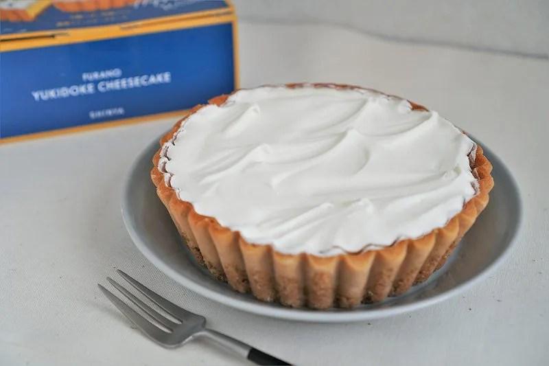 「ふらの雪どけチーズケーキ」が皿にのせられ、フォークと一緒にテーブルに置かれている