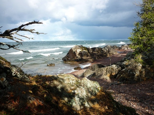 waves of Lake Superior roll to a rocky shore during the onset of a storm