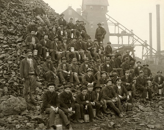 old black and white photo of about 30 mineres, sitting in tiers atop a pile of mining debri