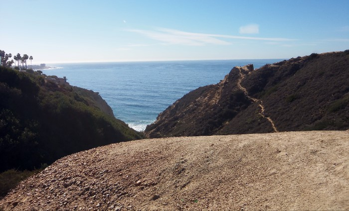 boulder in foreground. Ho Chi Minh Trail of La Jolla CA can be seen to the right. The pacific ocean is in background