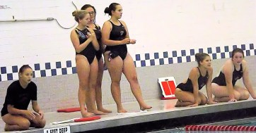 Members of team supporting their teammates in the pool