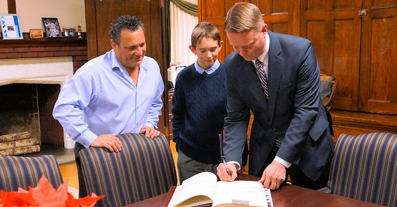William Baaki (right) signs an oath of office as his son Andrew (center) and Mayor Michael Villa (left) look on. Photo by Tim Becker.
