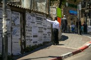 A Haredi man reads from the posters, known as 'pashkevilim', on a wall in the Bea Shearim neighborhood of Jerusalem. The pashkevilim are used to communicate news, opinions, and moral dictates from different rabinic groups within the Haredi communities. Photo: Gustavo Martínez Contreras|30 May 2016