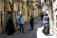 """A man moves out of the way and another covers his face as a woman in burqa-style veil walks in a street if the Mea Shearim neighborhood of Jerusalem. The """"frumkas"""", a sect that claims to bring back an ancient level of modesty among the Haredi, are highly criticized by the larger community. Photo: Gustavo Martínez Contreras