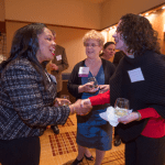 Women's Justice Award honoree Loretta Haggard, center, looks on as past recipient Nicole Colbert-Botchway,  on left, introduces herself to Natalie Teague, on right. Haggard was recognized in the Litigation category for her work at Schuchat, Cook & Werner, where Teague also works.