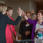 Deborah Dodge, on left, and Stacey Naeger, on right, high five while talking with Alice Conway. Dodge was honored for her litigation practice and Conway in the Enterprise category.
