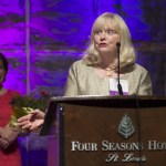Attorney Virginia Fry, center, accepts her award as the  Woman of the Year at the 2015 WJA awards banquet at the Four Seasons Hotel in St. Louis Thursday April 30th.  Fry is an attorney with Husch Blackwell in Springfield, Mo.  Missouri Supreme Court Chief Justice Mary Russell made the introduction and stands in back holding her flowers.