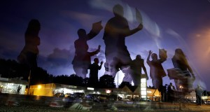 In this Aug. 20, 2014 file photo taken with a long exposure, protesters march in the street as lightning flashes in the distance in Ferguson. AP