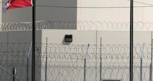 This Friday, Aug. 26, 2016 photos shows a look down Highway Terrace in Leavenworth, Kan., at the main gate of the Leavenworth Detention Center of Corrections Corporation of America. Defense attorneys who represent inmates at a privately run federal prison in Kansas were livid after learning that their meetings with clients had been recorded on video. (AP Photo/Orlin Wagner)