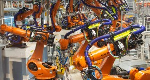 In this Tuesday, May 14, 2019 photo, robot arms stand at the assembly line during the reconstruction for the electrical car body construction at a press tour at the plant of the German manufacturer Volkswagen AG (VW) in Zwickau, Germany. Volkswagen will total shift into electric cars at the plant in Zwickau and the first vehicles are to roll off the assembly line at the end of 2019. (AP Photo/Jens Meyer)