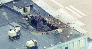 This Monday, April 3, 2017 photo from video by KMOV shows damage to the roof of a box company in St. Louis after a boiler exploded and flew before crashing through the roof of a nearby laundry business. Authorities said several people were killed as a result of the explosion. (KMOV via AP)