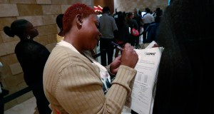 Esta Williams, center, uses Tracy Simeton's back to fill out a questionnaire as they wait in line at the Seminole Hard Rock Hotel & Casino Hollywood during a job fair in Hollywood, Fla. On Friday, Aug. 2, the U.S. government issues the July jobs report. AP Photo by Wilfredo Lee