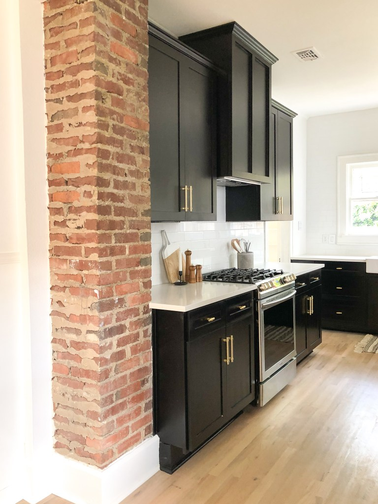 black and white kitchen design | floating shelves | brass hardware farmhouse sink | white subway tile | black kitchen cabinets | 102-year-old fixer upper house renovation | mid century modern Scandinavian home design | house flip reno