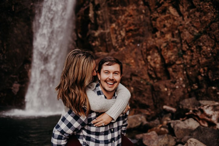 photo of piggyback couple at Franklin Falls in front of the waterfall