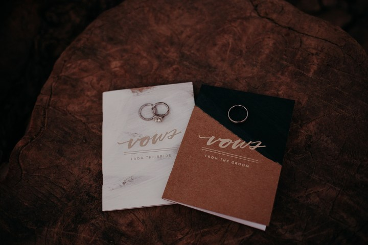 photo of vow books and wedding rings