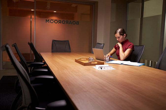 Young white businesswoman working alone late in an office