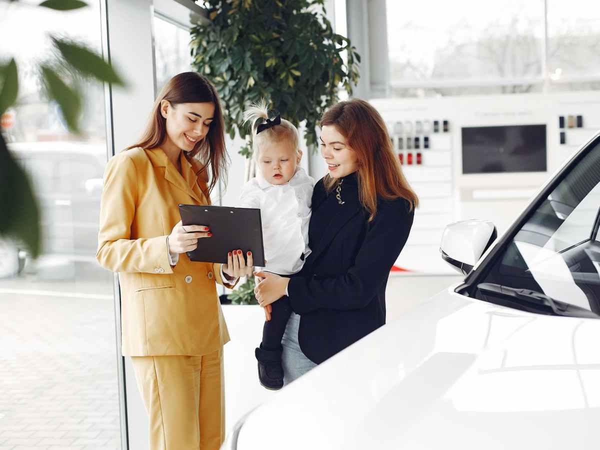 smiling mother choosing new car in car salon