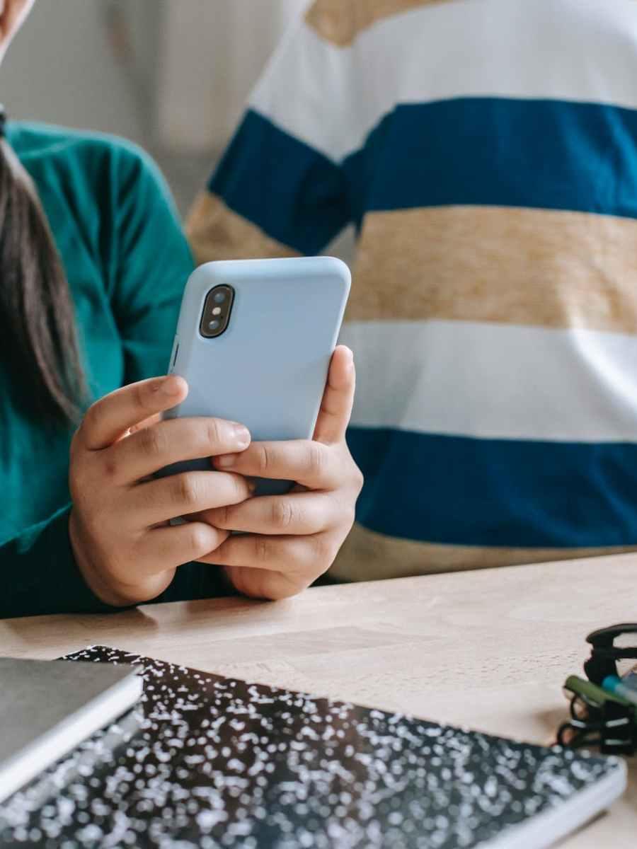 faceless schoolchildren watching video on cellphone during break in classroom