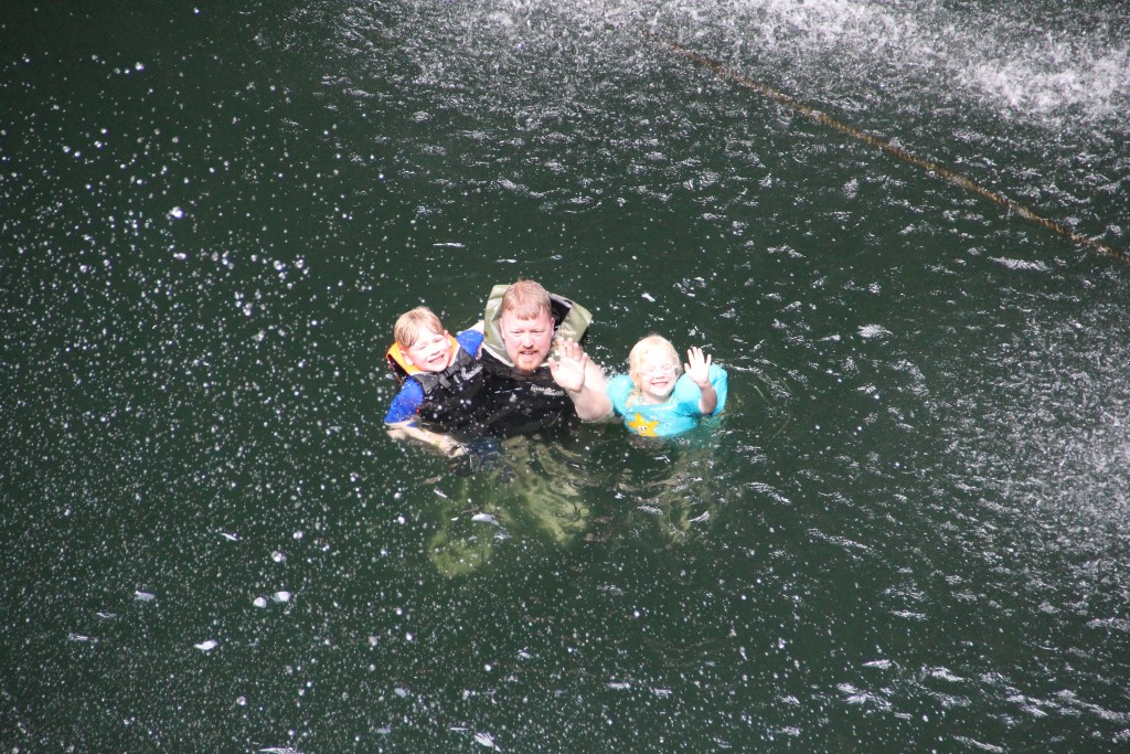 family waving in cenote